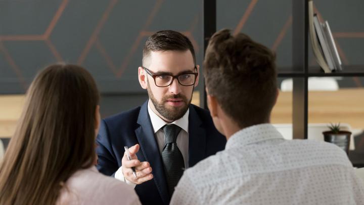 Anwalt im Beratungsgespräch mit zwei Personen