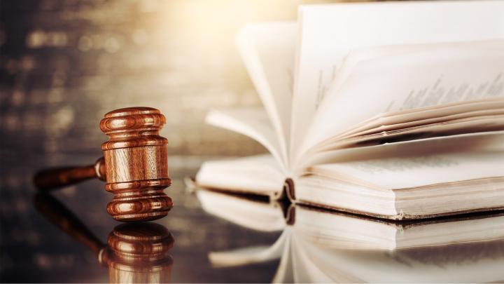 Richterhammer und aufgeschlagenes Buch liegen auf Tisch
