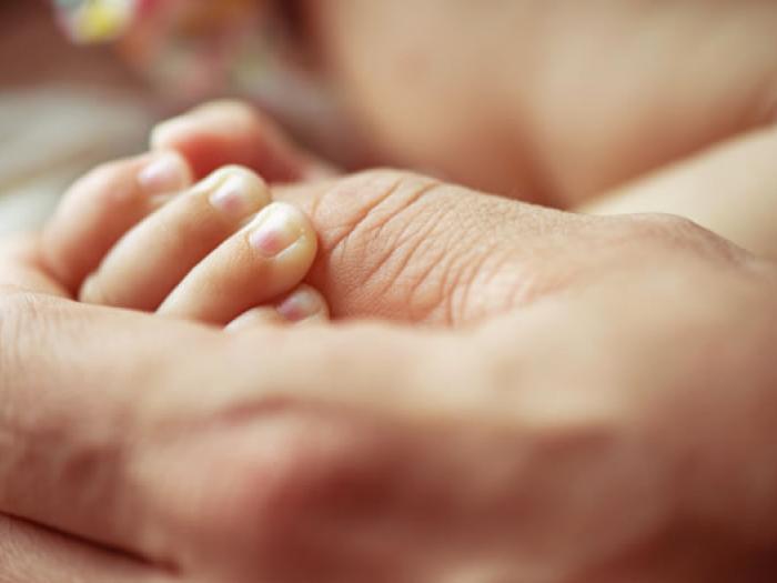 Erwachsene Person hält Hand von Säugling, Arzthaftungsrecht